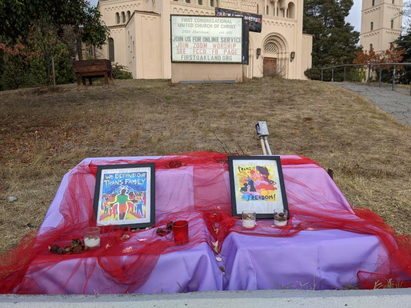 An altar set up in front of a church in Oakland, covered in pink, purple and red fabric. One framed image says 'We Defend our Trans Family,' the other says 'trans is freedom!'